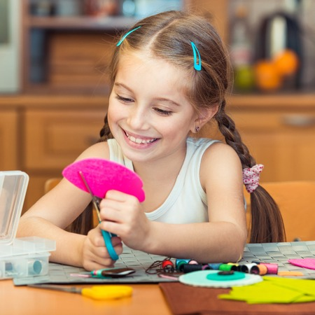 needlecraft product: happy cute little girl is engaged in needlework at home