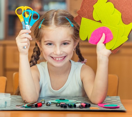 needlecraft product: happy cute little girl shows scissors and materials for needlework