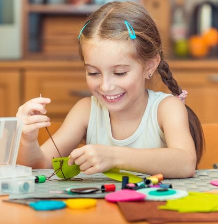 행복 한 귀여운 소녀 바느질에 종사하고있다