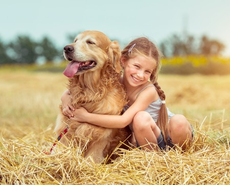 happy little girl with her dog golden retriever in rural areas in summer Banque d'images