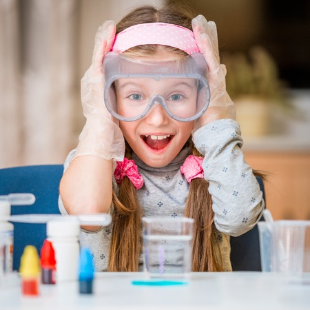 happy little girl with flasks for chemistry Фото со стока