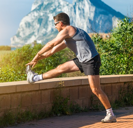 male athlete warming up before jogging on the sea background