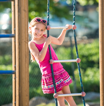 jungle gym: cute happy little girl on outdoor playground equipment