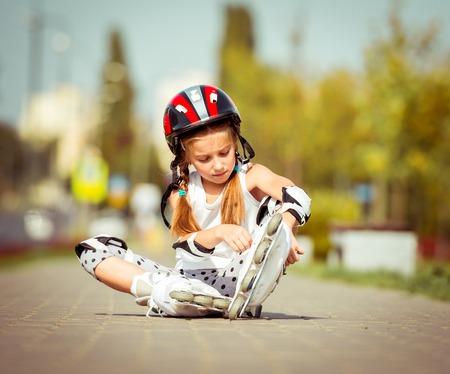 rollerskater: little cute happy little girl putting rollers