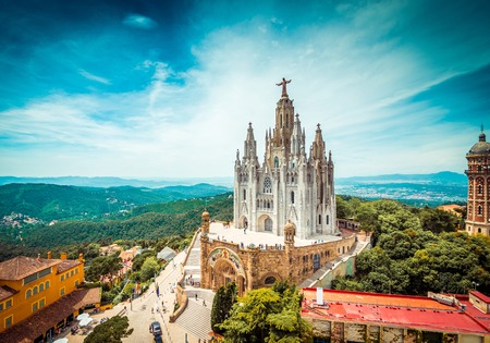 Tibidabo church on mountain in Barcelona with christ statue overviewing the city 写真素材