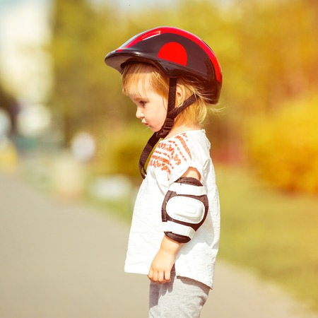 rollerskater: two year old pretty girl in a helmet on the street close-up