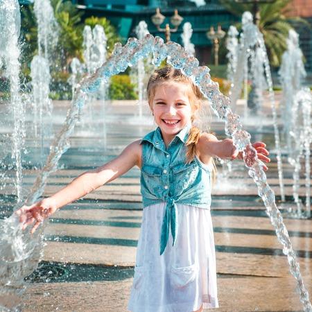 happy little cute girl having fun in splashes a fountain Foto de archivo