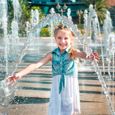happy little cute girl having fun in splashes a fountain Banque d'images