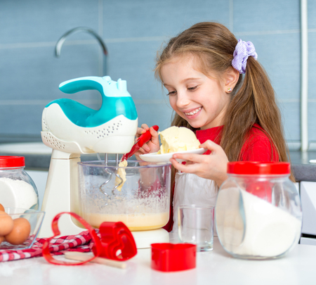 adds: preparing cookies to valentines day. little girl adds butter to the dough for cookies