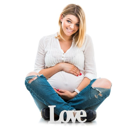 pregnant jeans: happy beautiful pregnant woman sit in blouse and jeans on white background