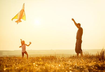 dadã  daughter: Papá con su pequeña hija dejó una cometa en un campo Foto de archivo