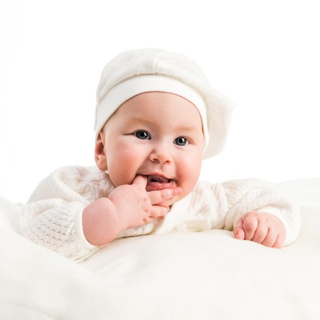 baby girl in a white cap and a jacket on a white background photo