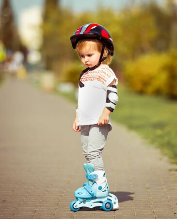 two year old: two year old pretty girl in roller skates and a helmet on the street
