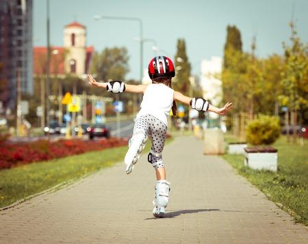 rollerskater: happy little girl on roller skates in the autumn forest