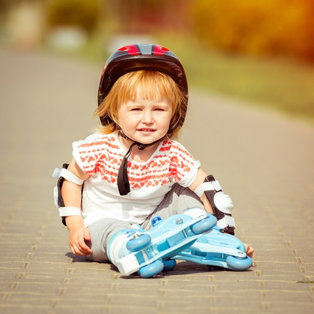 rollerskater: two year old pretty girl in roller skates and a helmet on the street