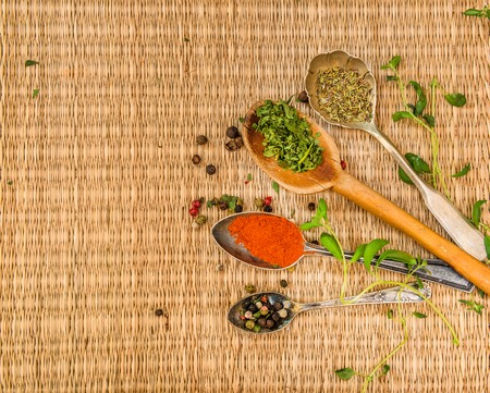 pounder: mortar with herbs and spices on a straw mat background