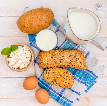 Breakfast of cheese, milk, bread and eggs on a light wooden background photo