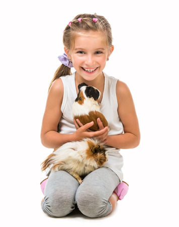 6 7 years: happy cute girl with a cavy. studio shot isolated on white background