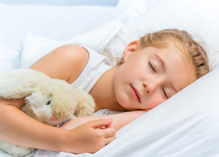 seven year old: Beautiful seven year old girl sleeping in white bed