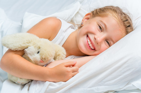 cute smiling little girl woke up in white bed Banque d'images