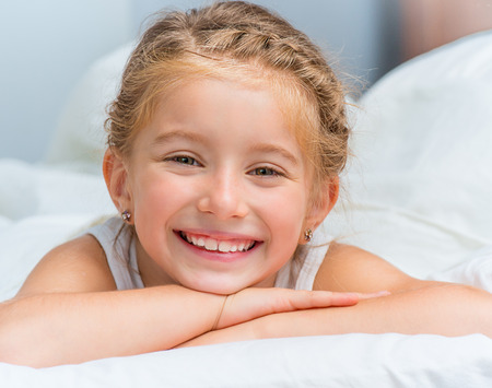 cute smiling little girl woke up in white bed Stockfoto
