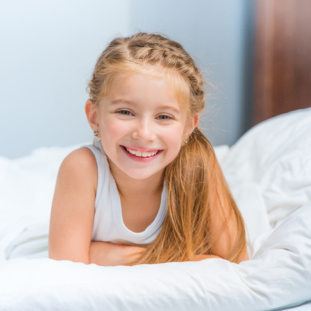 pretty little girl: cute smiling little girl woke up in white bed Stock Photo
