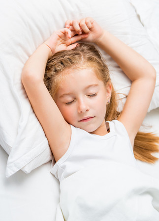 Beautiful seven year old girl sleeping in white bed photo