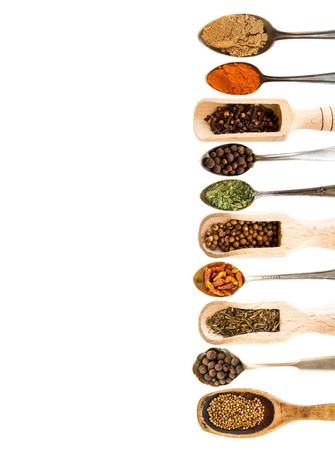 spoons with herbs and spices on white background