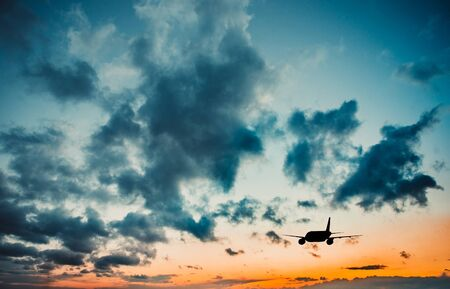 business class travel: Airplane in the sky at sunset Stock Photo