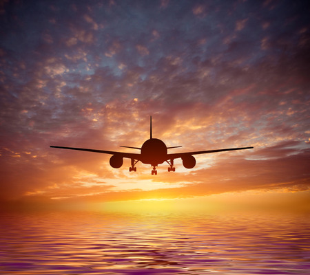 magnificent: aircraft flies over the ocean on a background of a magnificent sunset