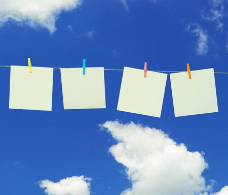 clothes pin: Clothes pin holding white sheets of paper outdoors