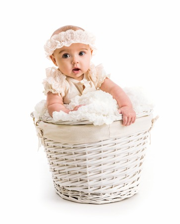 babycare: cute little girl in a wicker basket with lace headband