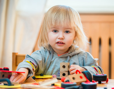baby girl: cute two-year old baby girl at home in the nursery playing with constructor Stock Photo