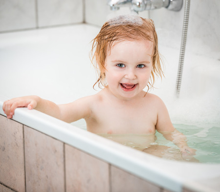 bathwater: cute two year old baby bathes in a bath with foam closeup Stock Photo