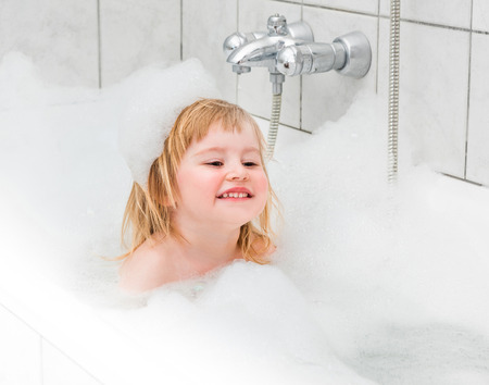 15 18: cute two year old baby bathes in a bath with foam closeup Stock Photo