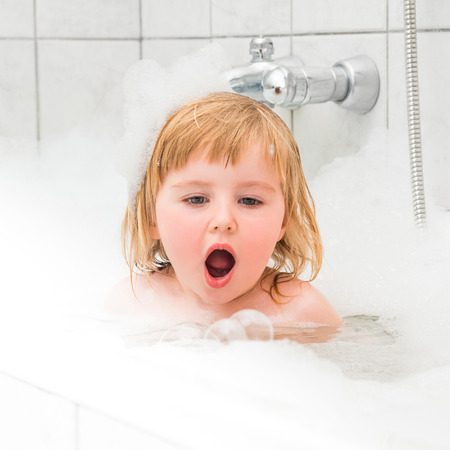 two year: cute two year old baby bathes in a bath with foam closeup Stock Photo