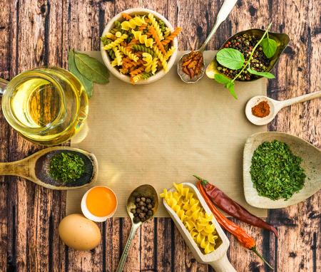 comida italiana: pastas alimenticias sin cocer y especias sobre un fondo de madera oscura