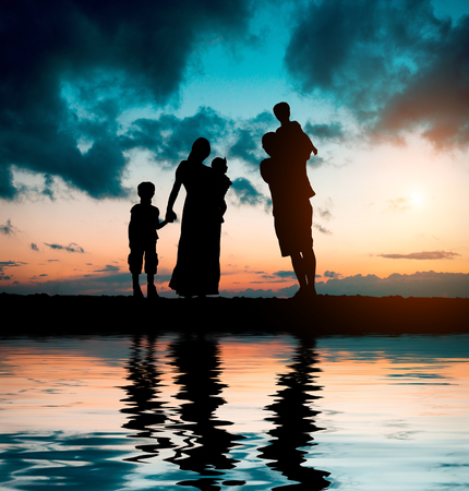 mother and child relationship: happy big family on a background of the magnificent sunset over the sea