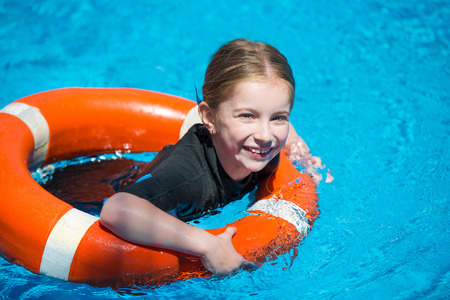 wetsuit: happy little girl swims in a wetsuit with a lifeline in the pool