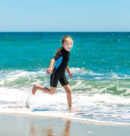 playing in the sea: laughing  little girl runing in a wetsuit on the seashore