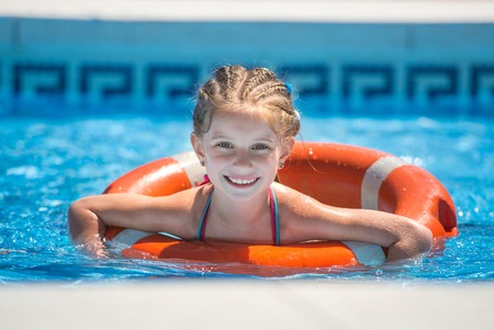 lifeline: happy cute little girl swims with a lifeline in the pool in  summer