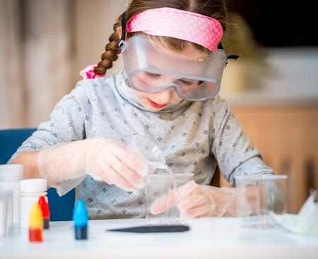 happy little girl with flasks for chemistry Standard-Bild