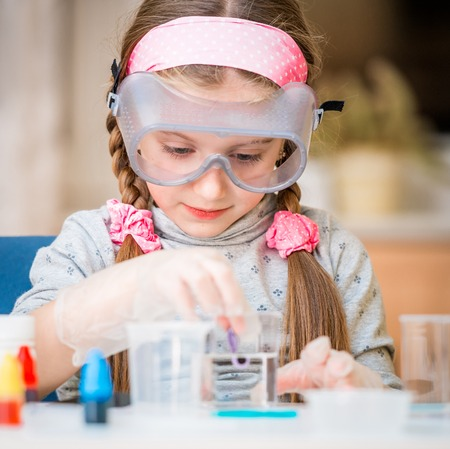 school test: happy little girl with flasks for chemistry Stock Photo