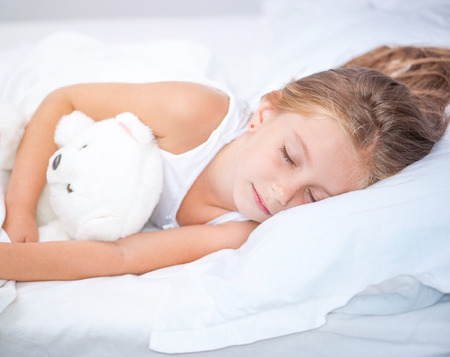 six year old girl sleeping in white bed with her teddy bear photo