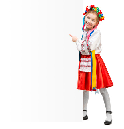happy little girl in the Ukrainian national costume stand behind white board with space for text