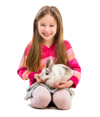 6 7 years: cute smiling girl in a crimson sweater  with baby rabbit over white background Stock Photo