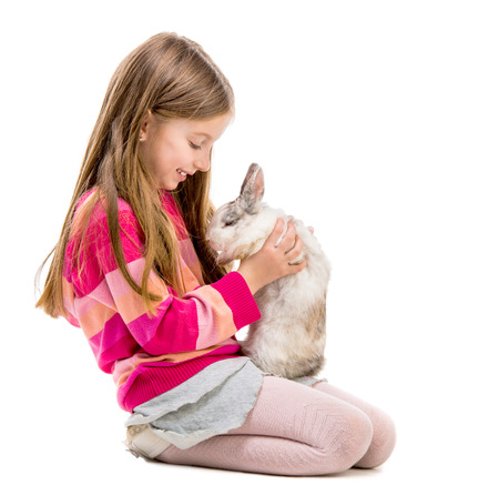 6 years girl: little girl in a crimson sweater  with baby rabbit over white background Stock Photo