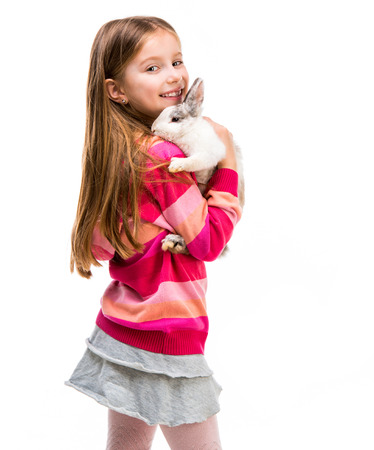 6 7 years: cute little girl in a crimson sweater  with baby rabbit isolated over white background Stock Photo