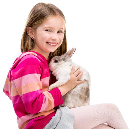conejo: sonriente niña en un suéter carmesí con conejo bebé aislados en blanco close-up