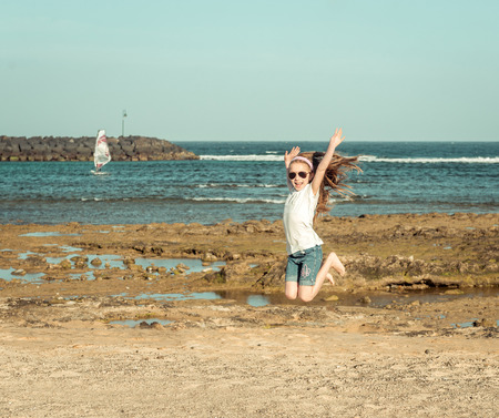 sitting pretty: little girl jump on a sandy beach